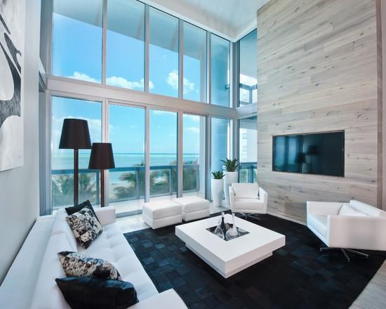 Sala clean em preto e branco, com luminaria de canto modelo abajour preto.
