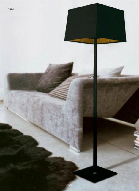 Sala com sofa cinza, luminaria abajour preta e tapete peludo no mesmo tom.
