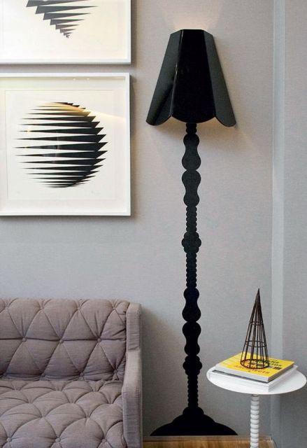 Sala com sofa cinza, parede no mesmo tom , luminaria abajour preta e quadro em cores preto e branco.