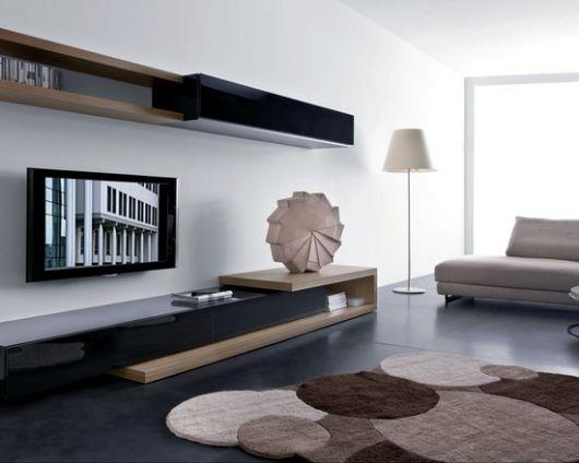 Sala na cor branaca, com moveis em preto e bege e abajour de canto branco.