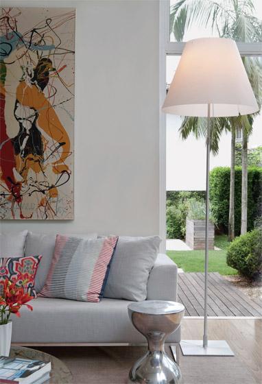 Sala com sofá cinza claro, paredes brancas, quadro colorido em tom de amarelo, bege e veremelho e luminaria abajour branca.