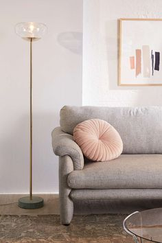 Sala com sofa cinza, paredes cinza clarinho e luminaria de piso sutil em tom dourado.