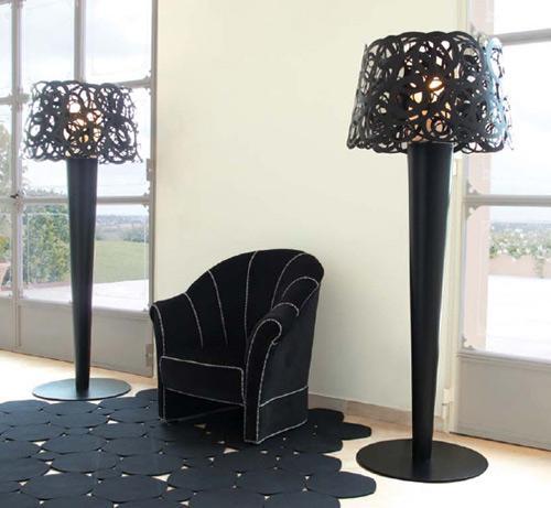 Ambiente com sofá preto, paredes brancas e duas luminarias modernas em tons de preto.