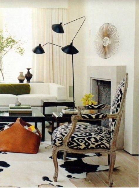 Sala branca, xom cadeira preto e branco de madeira e luminária de chão no tom de preto.