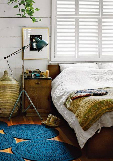 Quarto em tons de branco, amarelo e azul, com luminária retrô verde.