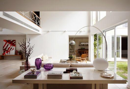 Sala clean nos tons de branco e madeira bege claro, com luminaria prata modelo arco.