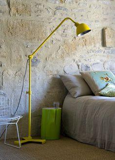 Quarto com parede trabalhada na cor de pedra cinza e luminaria de piso amarela.