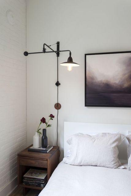 Quarto branco com quadro ao fundo em tons de roxo, luminária exótica de chao na cor preta.
