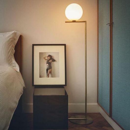 Quarto em tons de azul, bege e branco, com luminaria de canto, minimalista de formato redondo nas cores de dourado.