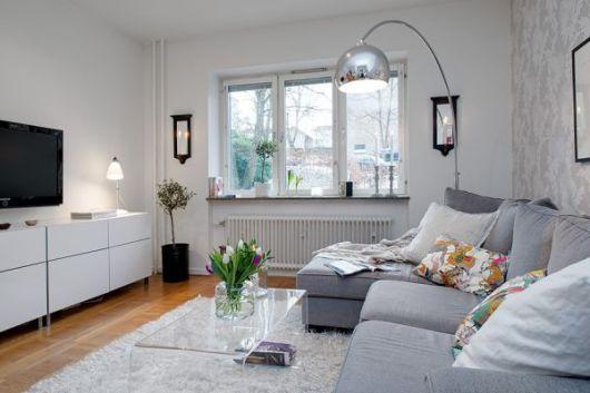 Sala na cor branca com móveis no mesmo tom, com sofá cinza e luminaria prata.
