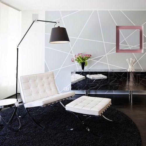 Sala com cadeira branca, tapete preto, e decoração cinza, com luminaria preta articular.