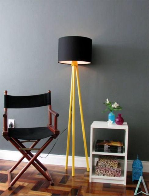 Sala cinza, com movel branco e luminária em tons de preto e amarelo com tripé.