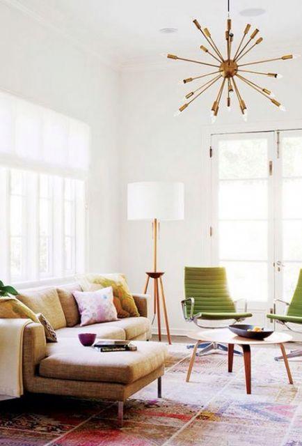 Sala clean com sofa bege, cadeiras verdes e luminaria de piso com tripe de madeira e cupula branca.