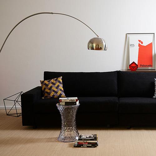 Sala com sofá preto, luminaria dourada.