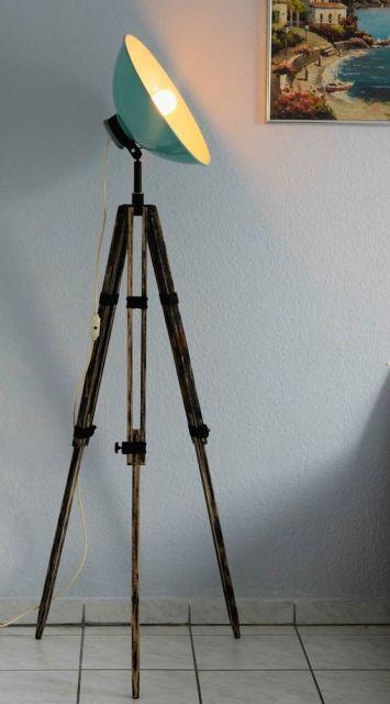 Luminária nas cores verde antigo, com luz amarela e tripé em metal.