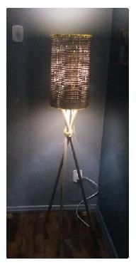 Luminária de vime na cor preta com tripé de madeira no mesmo tom.