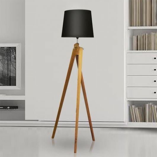 Luminária nas cores de preto, com tripé em madeira na cor bege amarelado.