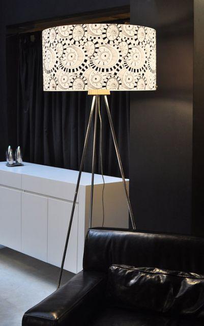 Luminária estampada em tom de branco e preto, com tripé em metal na cor prata.