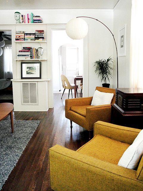 Sala branca, com sofas em amarelo e luminaria branca de chão.