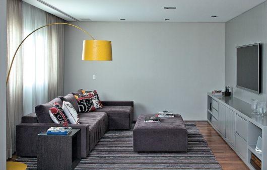 Sala na cor cinza, sofa no mesmo tom e luminaria amarela de chão.