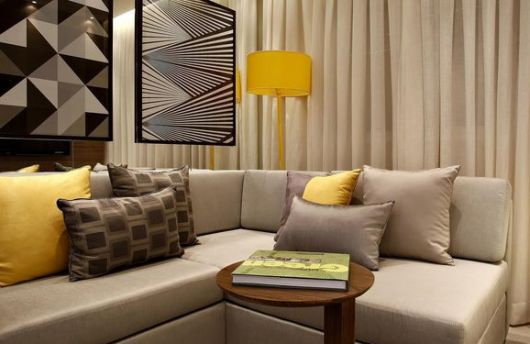 Sala bege com luminaria amarela de canto.