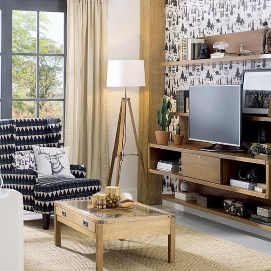 Sala rústica em tons de bege, sofá estampado e luminaria com abajour branco e tripé.