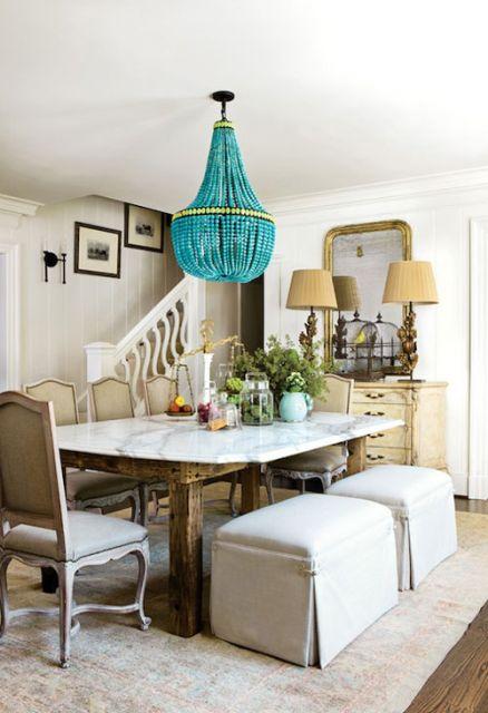 Lustre pendente azul no centro da sala de jantar.