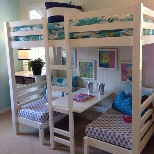 Treliche branco com escrivaninha e roupas de cama coloridas.