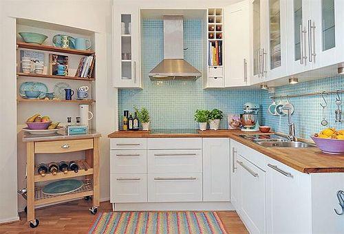 Cozinha com paredes azul claro ao fundo e pia de madeira.
