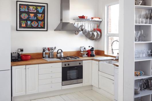 modelo de cozinha com balcão branco, detalhes de madeira, parede da cozinha em tons de branco também.