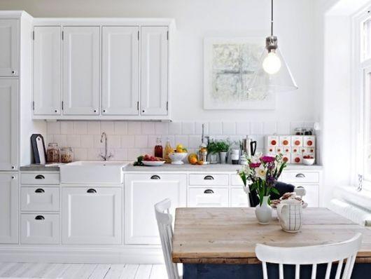 cozinha branca, com luz de mesa amarela, mesa de madeira.