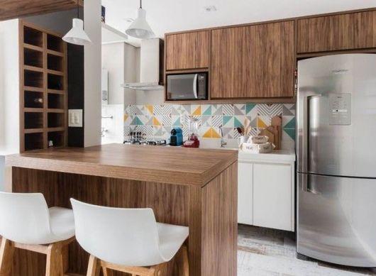 cozinha branca com móveis e balcão marrom escuro e detalhes coloridos naparede.