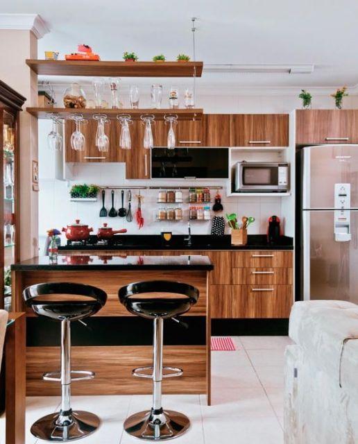 modelo de cozinha de madeira com alguns detalhes no armario e cadeiras na cor preta.