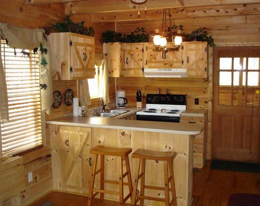 Cozinha amarela em tons de madeira, com fogão preto.