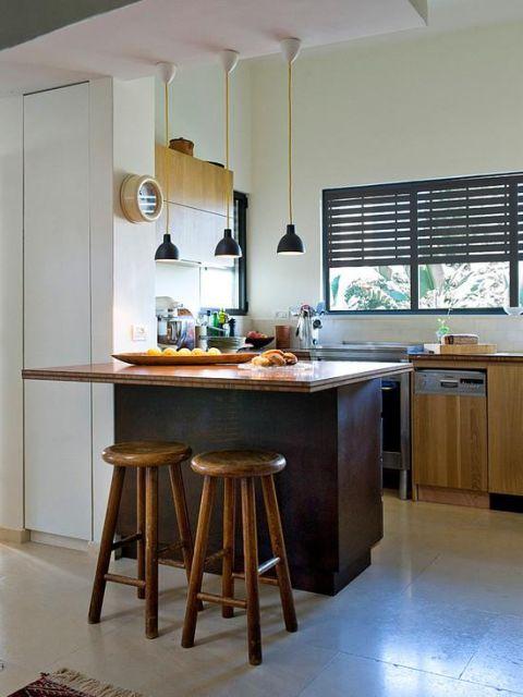 Modelo de cozinha pequena, simples com balcao marrom, banquetas no mesmo tom e parede branca.