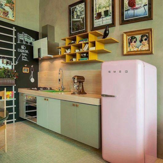 Modelo de cozinha verde com quadros espalhados na parede.