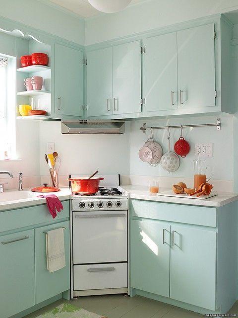 Modelo de cozinha verde clarinho com branco e detalhes de objetos vermelho e laranja.