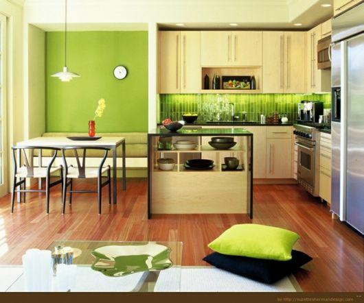 Cozinha verde limão com moveis de madeira e mesa branca.