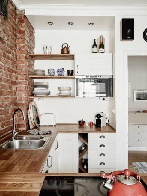 Cozinha com parede tijolo a vista, armarios branco e tons de madeira.
