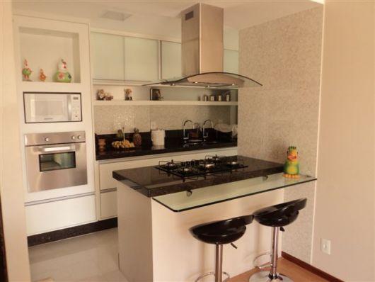 Cozinha toda em cor creme, banquetas pretas e fogao no mesmo tom das banquetas.