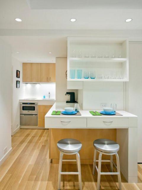 modelo de cozinha branca e amarelo com paredes clean, nicho branco e bancos cinza .