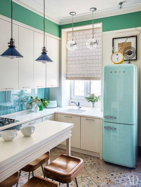 modelo de cozinha branca, com geladeira azul claro, luminarias azul escuro e detalhes de decoração verde nas paredes.