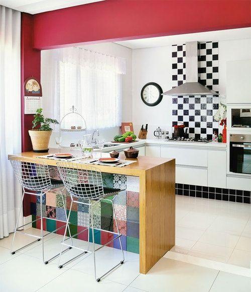 modelo de cozinha branca com detalhe em xadrez preto e branco na parede, com bancada colorida e banquetas de metal.
