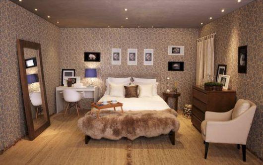 poltrona para quarto de casal em cor neutra na ponta da cama