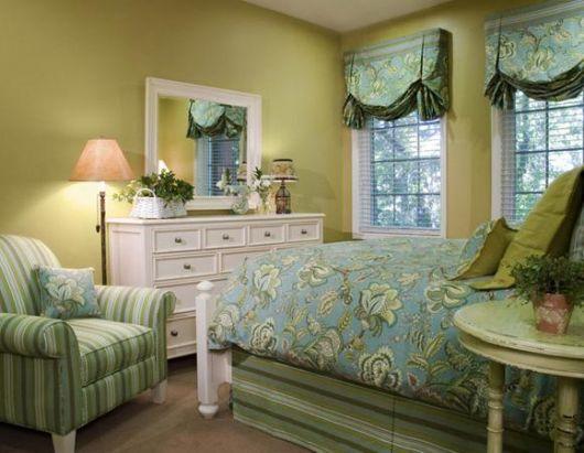 poltrona listradas em quarto de casal com colcha florida
