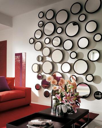 Sala com parede branca cheia de espelhos redondos pequenos, com sofa vermelho ao lado.