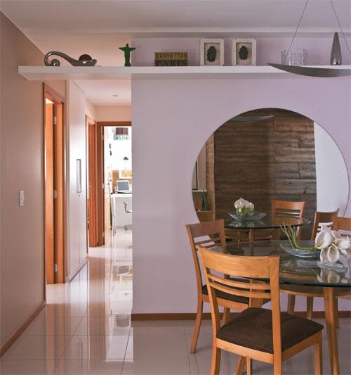 Sala de jantar com parede branca e espelho redondo amplo.