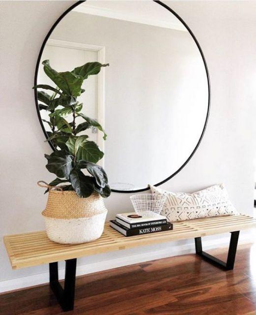 Hall com mesa de cão baixa e espelho redondo em parede branca.