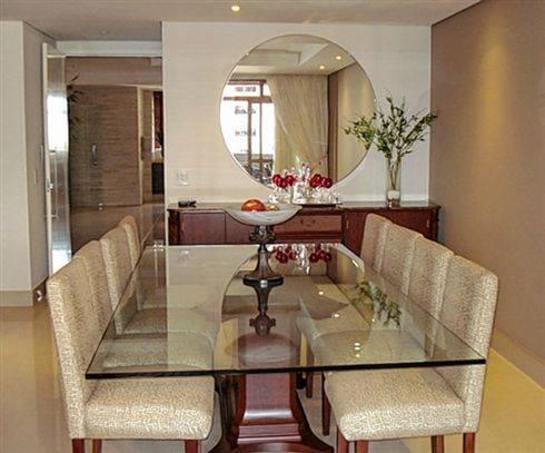 Sala de jantar com mesa quadrada, parede branca e espelho amplo redondo.
