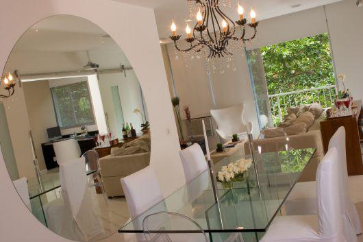 sala de jantar com parede all white, lustre e mesa de vidro.